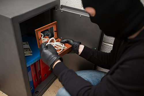 Thief stealing from safe - Home Insurance